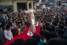 May 1996 - Modeling western wedding gown on Shanghai's Nanjing Road draws the attention of a large crowd of mostly men.   Photo by Fritz Hoffmann via National Geographic Proof