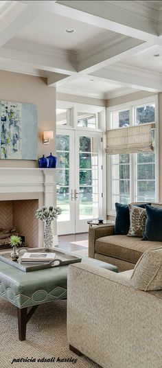 Coffered ceiling, open windows and doors, neutral furniture and accent coffee table, pretty fireplace