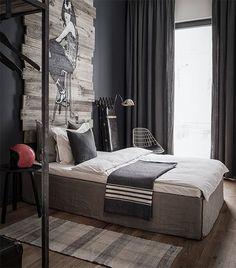 Um quarto jovem e com muita personalidade. A parede cinza dá característica ao ambiente ênfase aos demais elementos. Em destaque a arte na parede, em madeira..