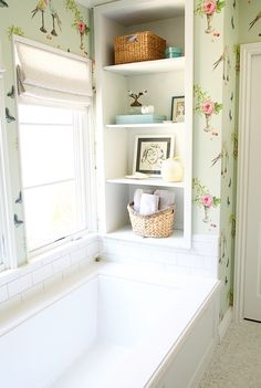 Bathroom with light green wallpaper with flowers and bird patterns, white bathtub with white tiles, tile floor, built-in shelves with art and decor details