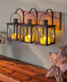 "Add the soft glow of candlelight to your home with this Rustic Wall Lantern or LED Candles. The Glass Lantern Wall Hanging (18-1/2""W x 7""D x 11-1/2""H) features three metal and glass lanterns hanging from hooks on a wooden plaque. LED candles not included"