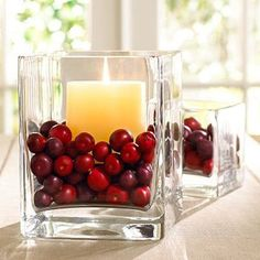 A festive fall centerpiece made from a glass cube vase, ivory pillar candle, and cranberries.