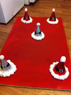 Santa Hat Toss! I made these for our Winter Festival. Very easy you need a board for the bottom, party hats, cotton balls, black paint and I put some bling for Santa's belt.