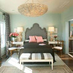 Something similar would be do-able in an apartment by arranging side tables with or without chairs on either side of the bed, curvy shaped headboard, painting walls, art behind the lamps on the table, bench, chandelier (lit or not), throw rugs, curtains hung high