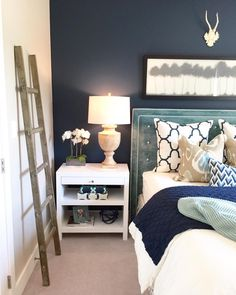 Bedroom with dark accent wall. Rustic ladder. Velvet headboard. Pattern pillows. Home decor blogger. Interior decorating. Home decor