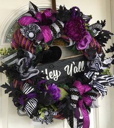 This Halloween wreath with Hey Yall sign makes quite Halloween door decor for any home. Done with shimmery striped Deco mesh all the way around, this perfect Halloween decoration is just what your door needs to greet those trick or treaters. A Wooden Hey Yall sign is secured in the center with handmade scented black velvet pumpkin on top. Surrounded by black glittery leaves, various printed ribbon bunches, greenery, and florals for a full lush look. The large Zebra print flower catches the…