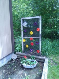 Old screen door frame. I used steel wool to clean it up, one coat of poly, and wood stakes screwed in the bottom to go into the ground. I used ''pet'' screen so it's a bit heavy duty, lightweight watering can I had laying around and fake daisies with a light gauge wire to put them on the screen.