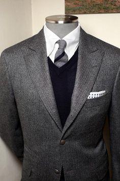 dark gray suit. white oxford. black cashmere sweater. black/gray striped tie. grey checked pocket square. classic.