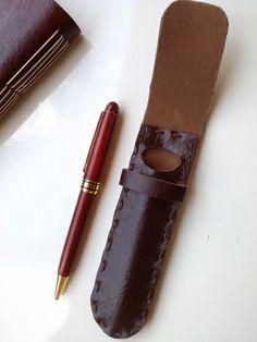 Porta caneta elegante, artesanal, peça única. Ocupa pouco espaço.  Perfeito para presentear. É possível personalizar com escrita (tinta dourada a mão). Feito de couro sintético marrom, todo costurado a mão.  Com alça de fechamento para proteger a caneta. Vem com caneta com corpo de madeira e carga substituível N116. Fácil de encontrar. R$ 35,00