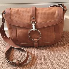 Sequoia cross body bag British tan 100% leather sequoia purse made in  Paris,  France. Adjustable strap. Very versatile. Sequoia bags have a signature ring somewhere on their bags. Beautiful bag. I just do not use. Only flaw is a slight darkening of leather on bottom of bag, shown in pic 4. Priced to sell. Sequoia Bags Crossbody Bags