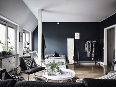 In this studio apartment a black wall is used to outline the sleeping area.