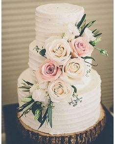 Rustic wedding cake adorned with blush florals on wood slice cake stand #weddingcake #rusticwedding #rusticweddingcake