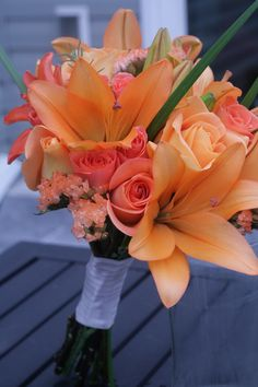 Orange bridesmaid bouquet with roses and lilies