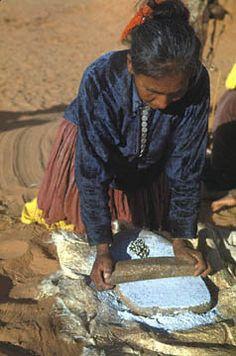 Navajo woman grinding blue corn on metate.