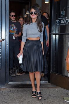 Selena Gomez wears a gray long-sleeved crop top and a black leather pleated skirt with black strappy sandals