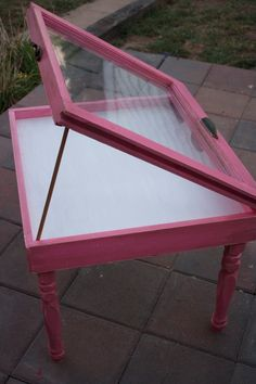 This is a shadowbox table made from an old window. The window came out of a Saint Louis City home, and has been repurposed to create a unique shadowbox table. The inside of the table has been white washed. The outside has been painted an pink and has been distressed.