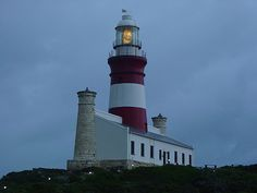 This lighthouse perches at the southernmost tip of all Africa and acts as the official dividing point between the Indian and the Atlantic Ocean. Built in it was designed as homage to the famous Lighthouse of Alexandria. -L'Agulhas Lighthouse- South Africa Places Around The World, Around The Worlds, Famous Lighthouses, Lighthouse Lighting, Beacon Of Light, Light Of The World, Famous Places, Atlantic Ocean, Adventure Is Out There