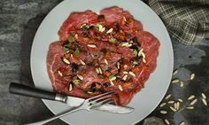 beef carpaccio with tomato, olives, pine nuts and basil. Jacob Kennedy