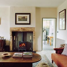 A cosy Country Modern White Living Room Design Idea with wood burning stove in the original fireplace and modern rustic furniture. Living room ideas.