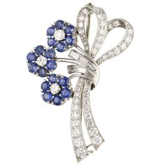 RAYMOND YARD Estate Platinum Diamond Sapphire Flower Brooch. Vibrant and charming estate platinum set sapphire and diamond brooch clip designed as a bouquet of flowers, by Raymond Yard. It features approx. 2.0 cts of very high grade sapphires (very rich and lively blue) and approx. 1.75 cts of high grade diamonds (both round brilliant and tapered baguette cut).  Hallmarks: Yard. c 1950s