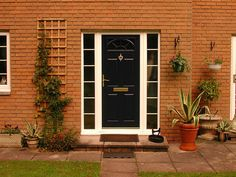 Blue classic GRP door with gold furntiure and white uPVC side panels