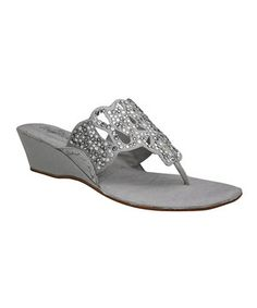 Promenade in high-fashion style with these sandals. Dotted with shiny accoutrements, this luxe leather pair boasts a slip-on silhouette and a leg-elongating wedge.