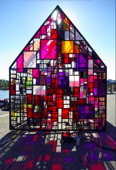 Colorful glass house.. Tom Fruin, a New York-based installation artist, recently traveled to Copenhagen where he built this stunning outdoor pavilion in plaza outside of the Royal Danish Library. Constructed out of hand welded angle iron and about a thousand scraps of reclaimed plexiglass, Kolonihavehus is a portable structure commissioned by CoreAct