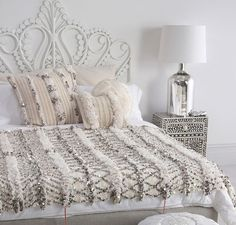 A bed adorned by a Moroccan wedding blanket and matching cushions.