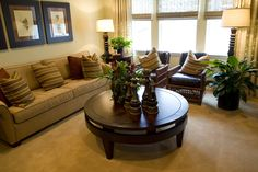 This sand toned living room features bamboo and dark leather chairs, light brown fabric couch, and a large, circular coffee table with greenery all around.