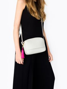 Gray leather crossbody bag with a pink suede tassel.