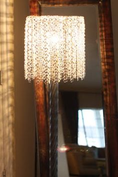 Lamp shade made from pop tops from soda cans. Throws chandelier like sparkles when lit.