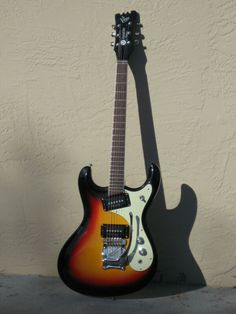 """The real Mosrite Gospel """"The Ventures"""", in sunburst. It's a mid sixties guitar and it's called after the popular surf rock band. Univox copied this first (and then evolved the design) and obviously Eastwood had a copy for this (or THAT HI flyer) too, a while ago. And it was even cheaper than the current Phase 4 guitar."""