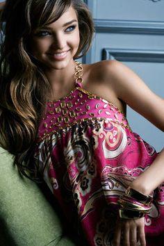 Brunette supermodel Miranda Kerr sitting in a pink pattern frock