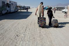Two people pull their suitcases through the sand as they make their way home, after the conclusion of Burning Man 2012, on September 2, 2012. (Reuters/Jim Urquhart) #