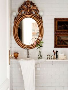 beautiful bathroom with oil paintings and an antique mirror
