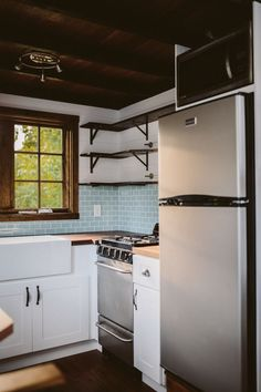Tiny house kitchen includes 3/4 refrigerator, microwave, and oven. Custom welded open shelving and seaglass subway tile. The Mayflower by Wind River Tiny Homes.