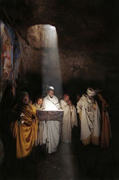 Monks read the Bible at noon, when sunlight shines through the hole in the roof of a church carved out of rock, Abuna Aron, Ethiopia