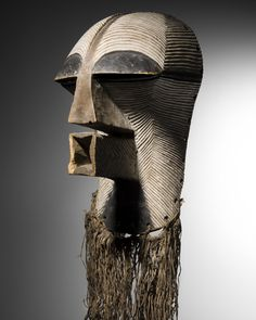This ceremonial mask with square mouth embodies mystical power. It was carved in wood by the Songye of the Democratic Republic of Congo, with a grooved pattern, white patina and raffia. Presented at Brafa 2017 by Galerie Monbrison.