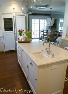 Stunning white kitchen renovation - carrara marble counters, red stove, and glass refrigerator!  ecleticallyvintage.com