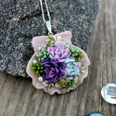 Succulents flowers composition in the sea shell, original silver pendant