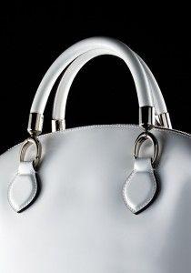 Close up of the handles of a white leather handbag.  Luxury fashion accessories / handbags. Still life photographer David Parfitt www.davidparfitt.com