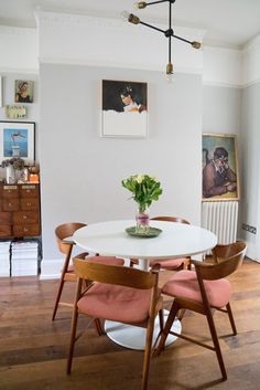 Dark wooden flooring goes beautifully with pale grey walls in this dining room #PinkChair