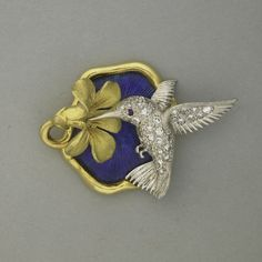 "SCHULER-MCTEIGUE JEWELED GOLD AND PLATINUM ORNAMENT, 1975-1991; Diamond pave platinum hummingbird with ruby eye sips nectar from sculpted 18k yg. blossom above blue guilloche enamel ground; 7.0 dwt. (10.9 gs.), 1 3/4""; Note: McTeigue & Co. was founded in NY in 1895, as a manufacturer of fine diamond jewelry"