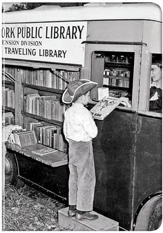 boy in cowboy hat standing on step to get a book from a New York Public Library bookmobile, c. 1950, NYC, USA