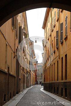 Photo made in Parma (Italy). In the picture you see, beyond the arc, one of the narrow streets of the old city surrounded by the typical palaces of the city with no shops or restaurants.