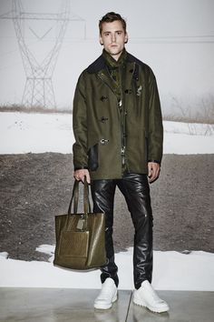 A look from the #CoachMens2015 presentation: the Military Cotton Fireman Coat, Grey Heather/Grass Ringer T-Shirt, Black Leather Jeans, Military Wild Beast Scarf, Black Cord Pouch, Lo-Top and Loden Bullneck Small Tote