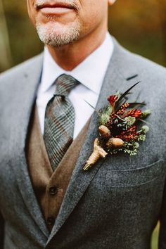 a white shirt, a checked tie, a tan waistcoat and a grey tweed jacket