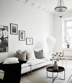Vardagsrum i sekelskifte, vit soffa och svarta detaljer