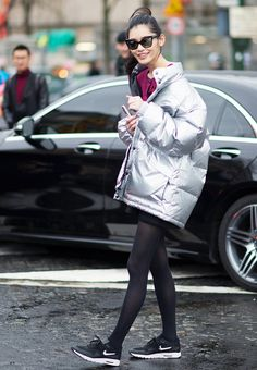 Model Ming Xi wears a pink sweater, black dress, silver puffer jacket, tights, and Nike sneakers