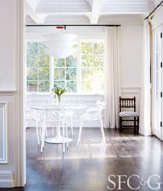 Dining space with wood floors, white walls, white curtains, white kitchen table, white light fixture, and white chairs